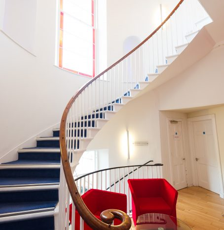 Photo of a winding staircase with red chairs at the bottom.